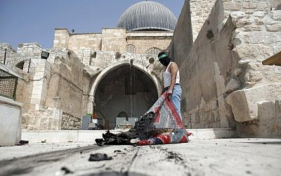 A masked Palestinian wearing a Hamas headband takes a burnt carpet out of Al-Aqsa mosque in Jerusalem's Old City during clashes at the compound on September 13, 2015, just hours before the start of the Jewish new year. (AFP PHOTO/AHMAD GHARABLI)