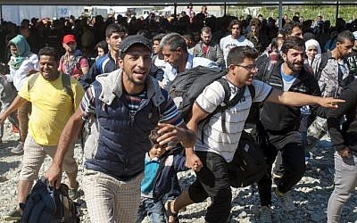 Migrants and refugees run to board a train after crossing the Macedonia-Greek border near Gevgelija on September 13, 2015. (Robert Atanasovski/AFP)