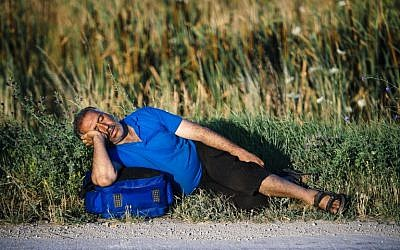 A migrant sleeps on a road near the southern Serbian town of Presevo, near the border with Macedonia, on July 15, 2015. (AFP/DIMITAR DILKOFF)