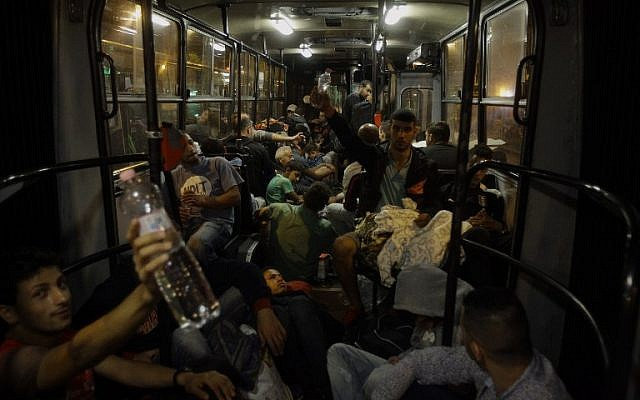 Migrant people sleep on a bus as they are transported from Budapest to the Hungarian village of Hegyeshalom, on the border with Austria, early on September 5, 2015. (AFP PHOTO/ PETER KOHALMI)