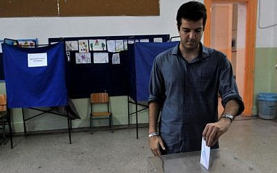 A young man casts his vote in a polling station in Thessaloniki, on September 20, 2015.  Greece's maverick leader Alexis Tsipras was fighting for a second chance to govern the struggling Eurozone nation in a tense election with rival conservatives that is proving too close to call.  (AFP/ Sakis Mitrolidis)