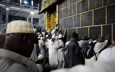 Muslim pilgrims touch Islam's holiest shrine, the Kaaba, at the Grand Mosque in Saudi Arabia's holy Muslim city of Mecca late on September 26, 2015 (AFP PHOTO/MOHAMMED AL-SHAIKH)