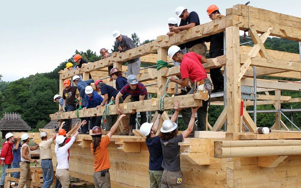 In Sanok, Poland, timber framers and students on the ground level using team work and collective human power to lift a finished log to a receiving team on the roof structure. (Trillium Studios production)