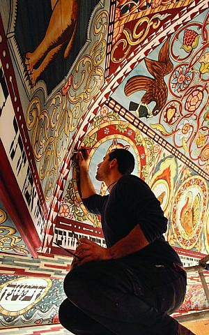 Jason Loik, painting leader, puts finishing touches on the Gwozdziec synagogue ceiling. (Trillium Studios production)