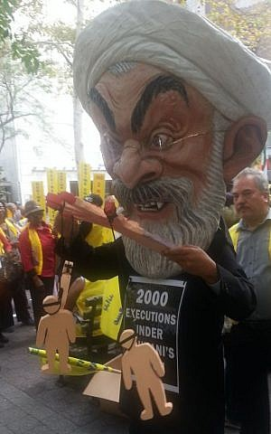 An anti-Rouhani protester dons a papier-mâché head of the Iranian president during a demonstration outside the UN building in New York, September 28, 2015. (Rebecca Shimoni Soil)