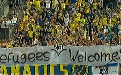 Fans of Maccabi Tel Aviv hold a banner with the text 'Refugees not welcome' during a match against Kiryat Shmona, on Saturday, September 12, 2015. (Screen capture: Channel 1)