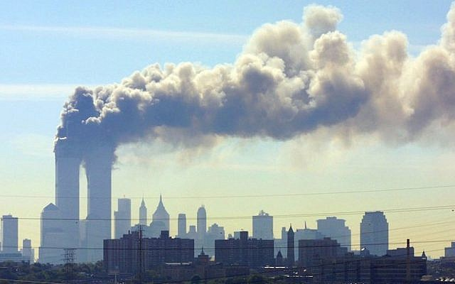 As seen from the New Jersey Turnpike, smoke billows from the Twin Towers of the World Trade Center in New York City after airplanes crashed into both towers, September 11, 2001. (JTA/AP/Gene Boyars)