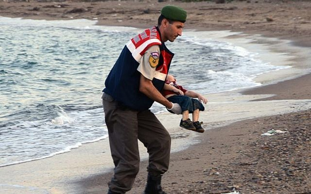 A paramilitary police officer carries the lifeless body of Aylan Kurdi, 3, after a number of migrants died and a smaller number were reported missing after boats carrying them to the Greek island of Kos capsized, near the Turkish resort of Bodrum early Wednesday, September 2, 2015. (AP/DHA)
