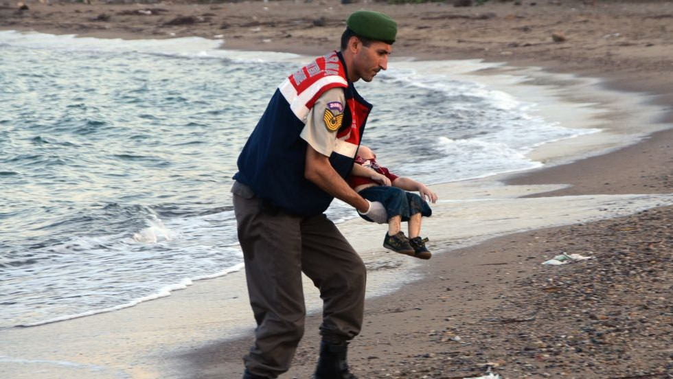 A paramilitary police officer carries the lifeless body of Aylan Kurdi, 3, after a number of migrants died and a smaller number were reported missing after boats carrying them to the Greek island of Kos capsized, near the Turkish resort of Bodrum early Wednesday, Sept. 2, 2015. (AP/DHA)
