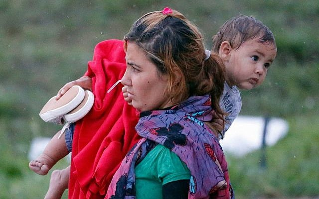 A migrant carries a child as they arrive at the Hungarian-Austrian border in Nickelsdorf, Austria, Saturday, Sept. 5, 2015, where they came from Budapest as Austria in the early-morning hours said it and Germany would let them in. (AP Photo/Frank Augstein)