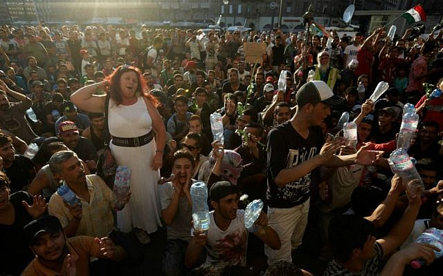 Hundreds of migrants wait in front of the Keleti Railway Station after police stopped them from boarding trains to Germany, Budapest, Hungary, Tuesday, Sept. 1, 2015. (AP Photo/Petr David Josek)
