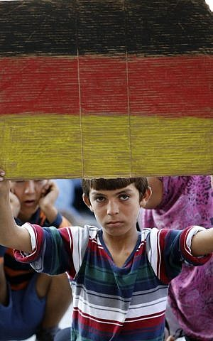 A young boy holds a German flag in front of the railway station in Budapest, Hungary, Thursday, Sept. 3, 2015 (AP/Frank Augstein)