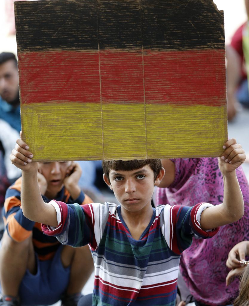 A young boy holds a German flag in front of the railway station in Budapest, Hungary, on September 3, 2015 (AP/Frank Augstein)