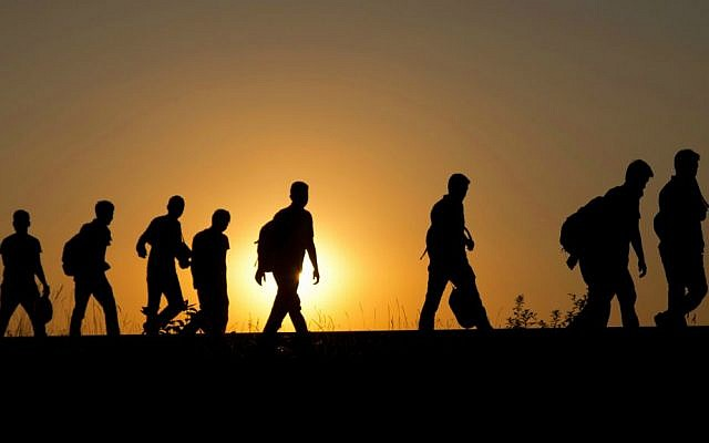 A group of refugees walk on the railway tracks after crossing from Serbia, in Roszke, Hungary, Tuesday, Sept. 1, 2015. (AP Photo/Darko Bandic)
