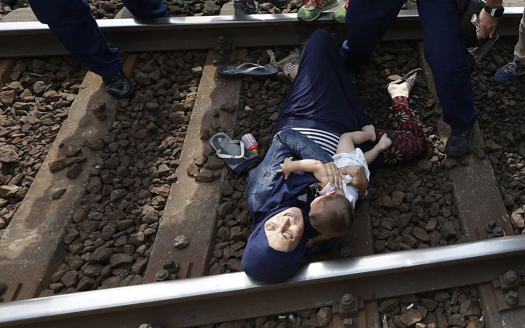 A migrant lies on the track with a baby as she is detained in Bicske, Hungary, Thursday, September 3, 2015. (AP/Petr David Josek)