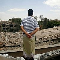 A man looks at the Houthi-controlled headquarters of the Yemeni army destroyed by Saudi-led airstrikes in Sanaa, Yemen,  September 16, 2015. (AP Photo/Hani Mohammed)