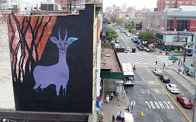 """A large gazelle mural is shown on the side of a building in the Harlem neighborhood of New York. The mural is one of about half a dozen that have been commissioned as part of a campaign to raise awareness for a nonprofit created by Maziar Bahari, the journalist who spent 118 days in an Iranian jail after an appearance on """"The Daily Show with Jon Stewart. The murals are being painted on buildings around the city as the United Nations General Assembly kicks off Tuesday, Sept. 15. Bahari hopes the art will attract the attention of diplomats and spark a conversation about human rights. (AP Photo/Mike Balsamo)"""