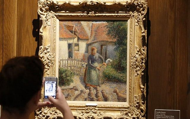 "A visitor to the Fred Jones Jr. Museum of Art at the University of Oklahoma takes a photograph of  ""Shepherdess Bringing in Sheep"" by Camille Pissarro on Saturday, February 8, 2014 (Sue Ogrocki/AP, File)"