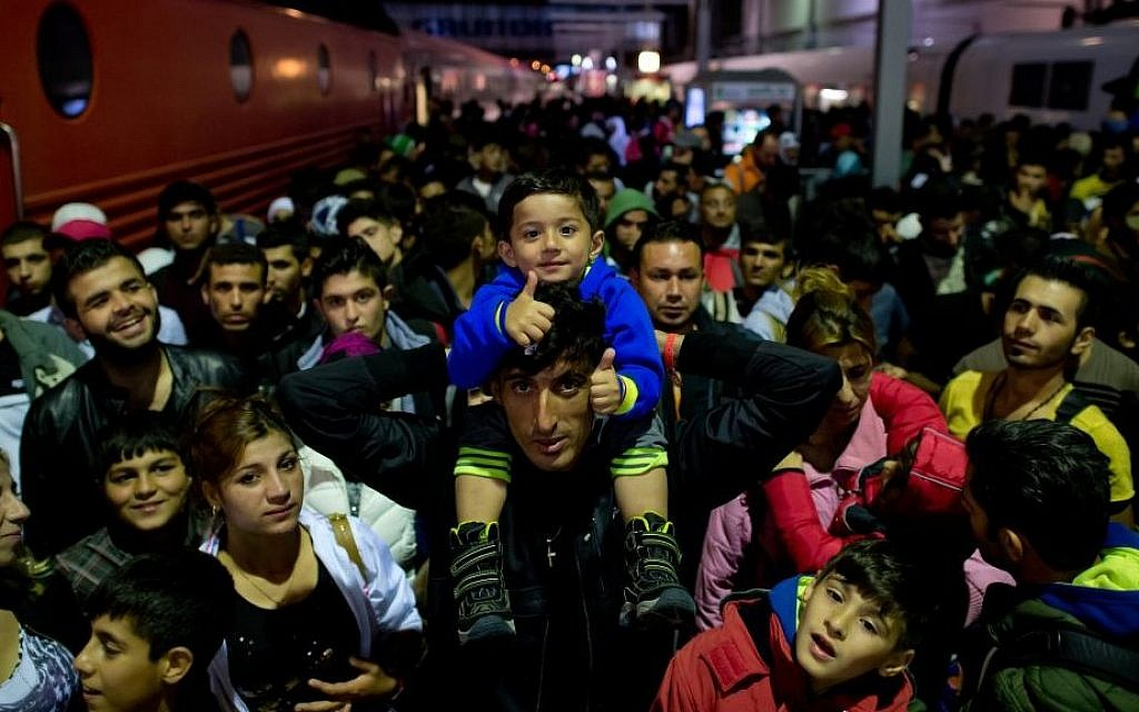 File: Refugees who arrived by train from Salzburg, Austria, wait on a platform at the central station in Munich, Germany, on September 6, 2015. (Photo by Sven Hoppe/dpa via AP)
