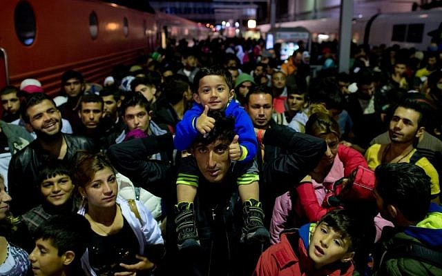 Refugees who have arrived by train from Salzburg, Austria, wait on a platform at the central station in Munich, Germany, on September 6, 2015. (Photo by Sven Hoppe/dpa via AP)