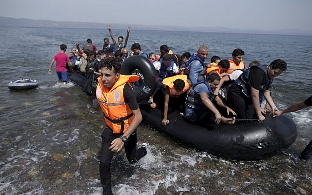Syrians arrive on a dinghy after crossing from Turkey, at the Greek island of Lesbos, Monday, September 7, 2015. (Petros Giannakouris/AP)