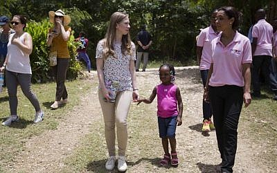Clinton Foundation Vice Chair Chelsea Clinton walks with Theresa Balde, 5, while she talks with a Chakipi Distribution Enterprise worker during a visit at the Acceso Peanut Enterprise Corporation and Chakipi Distribution Enterprise, in Mirebalais, Haiti, Wednesday, July 29, 2015. (Dieu Nalio Chery/AP)
