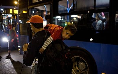 A man carries a child as they try to board a bus provided by Hungarian authorities for migrants and refugees at Keleti train station in Budapest, Hungary, Saturday, Sept. 5, 2015. Hundreds of migrants boarded buses provided by Hungary's government as Austria in the early-morning hours said it and Germany would let them in. (AP Photo/Marko Drobnjakovic)