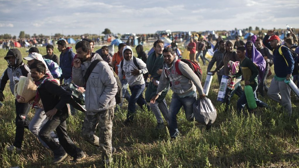 Migrants move away from a temporary holding center controlled by Hungarian authorities in Roszke, southern Hungary, Monday, September 7, 2015, inside Hungary, just over the border from Serbia. (Marko Drobnjakovic/AP)
