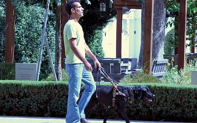 Blinded Israeli veteran Gadi Yarkoni confidently marches forward with his Hebrew-trained guide dog Timmy by his side.
