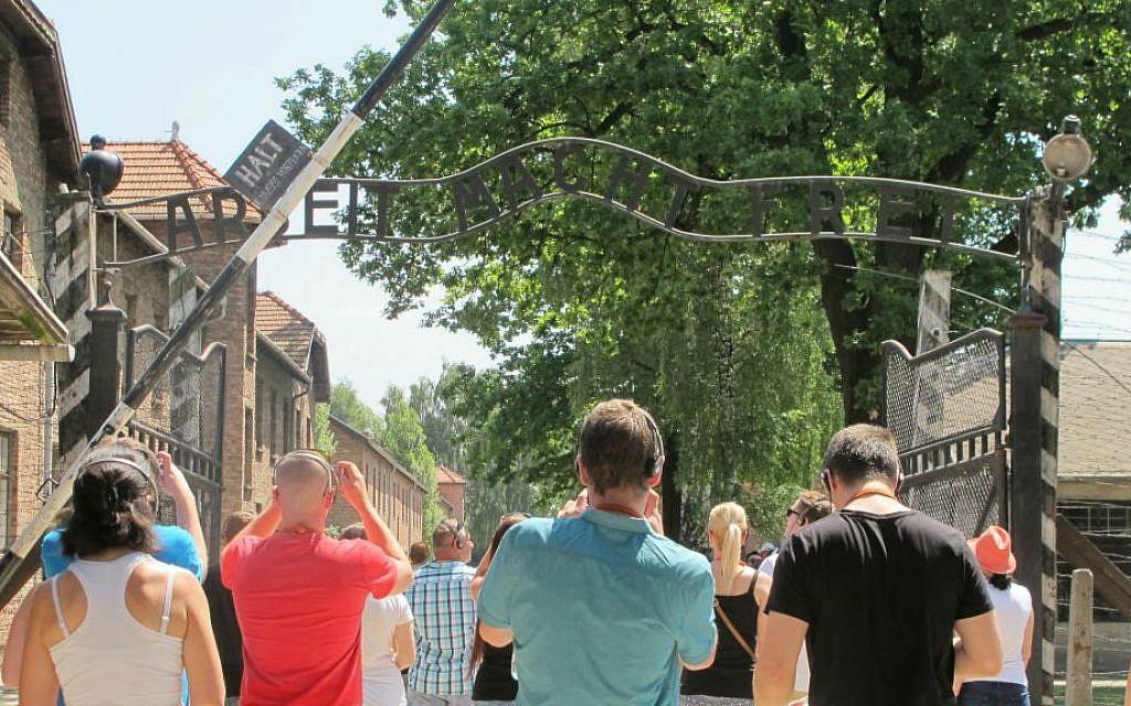 Tourists at Auschwitz photographing the 'Arbeit Macht Frei' gate, July 2015. (Ruth Ellen Gruber/JTA)