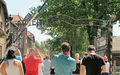 Tourists at Auschwitz photographing the 'Arbeit Macht Frei' gate, July 2015. (Ruth Ellen Gruber/JTA)
