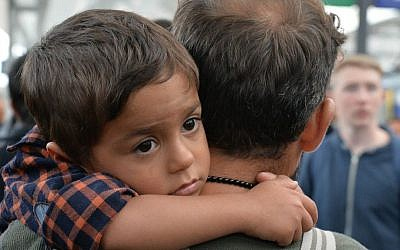A young migrant boy sits on the shoulders of a man as they arrive at the Hauptbahnhof station in Salzburg, Austria, Saturday, Sept. 5, 2015 on their way from Hungary via Vienna to Germany. (AP Photo/Kerstin Joensson)