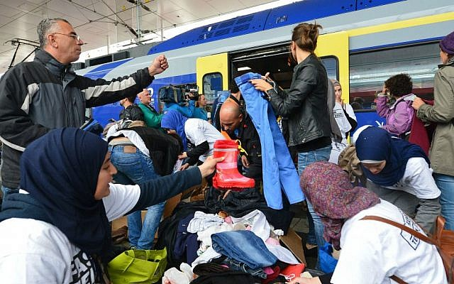 Refugees receive new clothes as they arrive at the Hauptbahnhof station in Salzburg, Austria, Saturday, Sept. 5, 2015 on their way from Hungary via Vienna to Germany. (AP Photo/Kerstin Joensson)