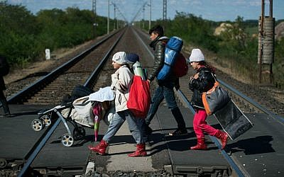 Migrants cross a railway on their way to the Austrian - Hungarian border near Hegyeshalom, Hungary, on Monday, Sept. 28, 2015. (AP Photo/Christian Bruna)