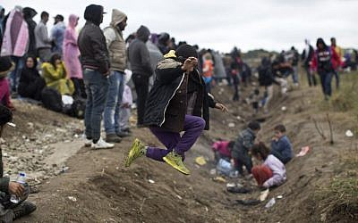 A child jumps over a ditch as people wait in order to clear a police line after entering Croatia from Serbia in Strosinci, Croatia, Saturday, Sept. 26, 2015 (AP Photo/Marko Drobnjakovic)