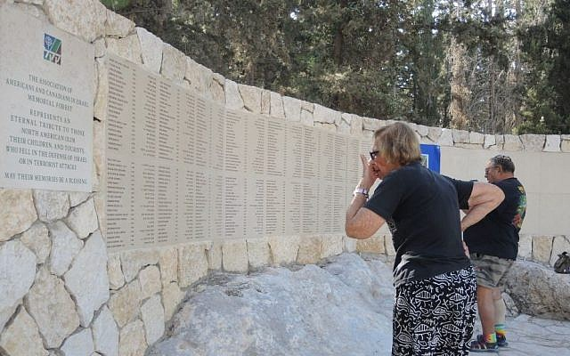 A participant in the annual AACI memorial reads some of the 335 names of Anglo victims of terror and wars before the ceremony started on Sunday, September 20, 2015, at the AACI memorial forest outside Jerusalem. (Melanie Lidman/Times of Israel)