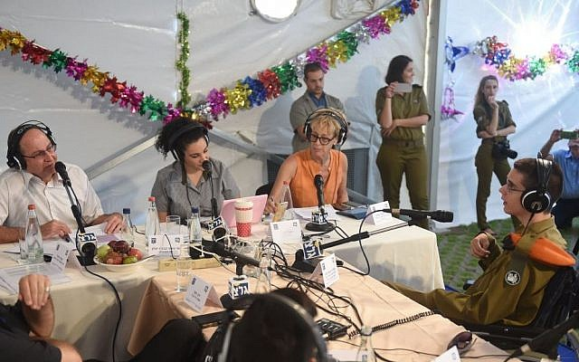 Defense Minister Moshe Ya'alon (left, in white shirt) being interviewed by Army Radio ahead of the Sukkot holiday, in the Defense Ministry's sukka in Tel Aviv. (Diana Hananshvili/Defense Ministry)