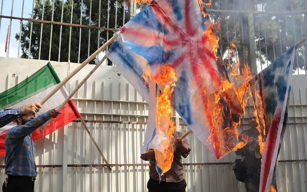 Iranians burn American, British and Israeli flags during the inauguration of an anti-American plaque displayed outside the former American embassy in Tehran on September 2, 2015. (Atta Kenare /AFP)