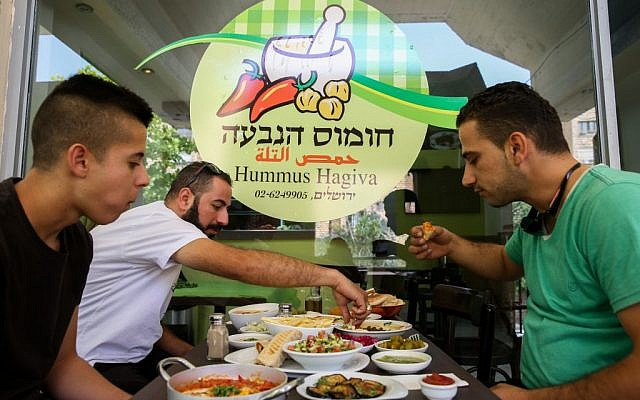 Palestinians eat Hummus at a Palestinian-owned restaurant in the predominantly Jewish neighborhood of French Hill, May 27, 2015 (Nati Shohat/Flash90)