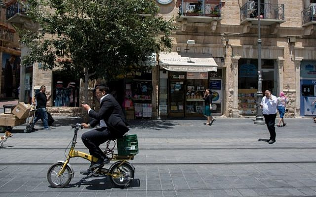 A man rides his bicycle along the train tracks on Jaffa Street in downtown Jerusalem, on June 24, 2015. (Yonatan Sindel/Flash90)