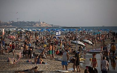 Illustrative: Thousands of Israelis and tourists seen on the beach in Tel Aviv on a hot summer day. July 25, 2015. (Miriam Alster/FLASH90)