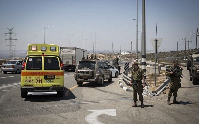 An ambulance evacuate a Palestinian man who was shot and lightly injured after he stabbed an IDF  soldier at the 'Bell' Checkpoint, on Route 443, August 15, 2015. (Hadas Parush/Flash90)