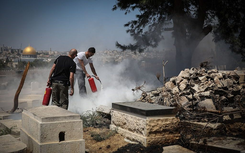 Security personel try to extinguish a fire which broke out at the Jewish cemetery on the Mount of Olives, where several tombstones were allegedly desecrated and set on fire overnight, September 2, 2015 [Hadas Parush/Flash90]