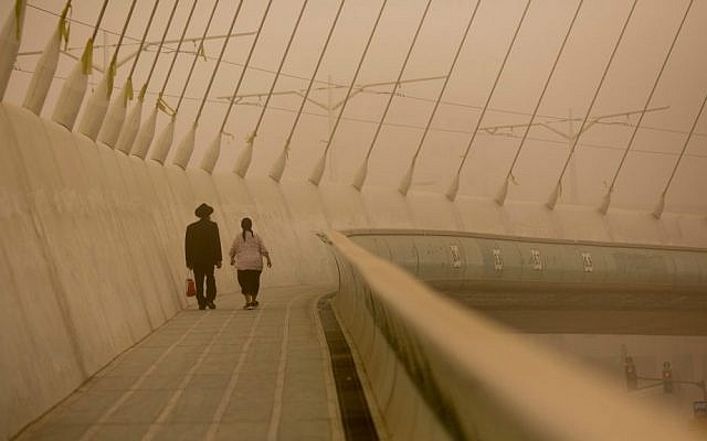 Residents walk near the Chords Bridge in Jerusalem, September 8, 2015, as a sandstorm settles on the city. (Yonatan Sindel/Flash90)