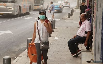A woman wears a mask to cover her mouth on a dusty day in Tel Aviv September 09, 2015. (FLASH90)