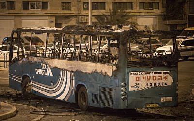 A bus set on fire, apparently by petrol bombs, at a roundabout in the East Jerusalem neighborhood of Ras al Amud, near Mount of Olives, on September 17, 2015. The bus driver took a wrong turn, entered the Palestinian neighborhood and his bus was attacked with stones. The bus was empty of passengers and the driver left it, and returned to find it on fire. (Photo by Hadas Parush/Flash90)