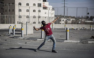 Illustrative photo of a Palestinian throwing a rock at Israeli Border Police during clashes in East Jerusalem on September 18, 2015. (Hadas Parush/Flash90/File)