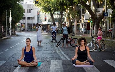 Israelis do yoga on an empty Tel Aviv street, on Yom Kippur, on September 23 2015. (Miriam Alster/Flash 90)