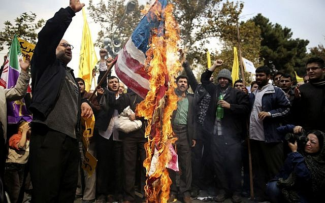 Iranian protesters burn an American flag during an annual anti-American rally in Tehran, Iran, Monday, Nov. 4, 2013.  (Ebrahim Noroozi/AP)