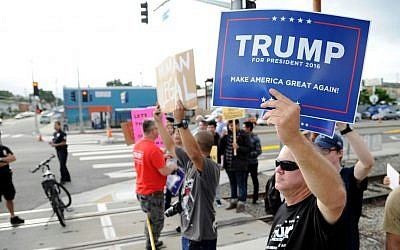 Supporters of Republican presidential candidate Donald Trump and demonstrators who are protesting against Trump's campaign appearance aboard the USS Iowa battleship meet across the street from the event site in Los Angeles, Tuesday, Sept. 15, 2015. (AP Photo/Kevork Djansezian)